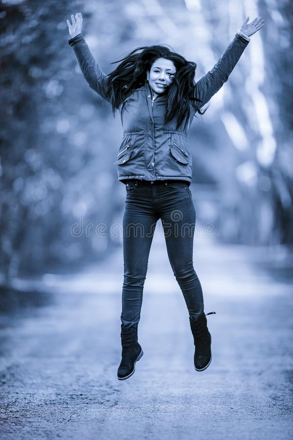 Jovem mulher com energia positiva e o sorriso bonito que saltam sobre fotografia de stock royalty free