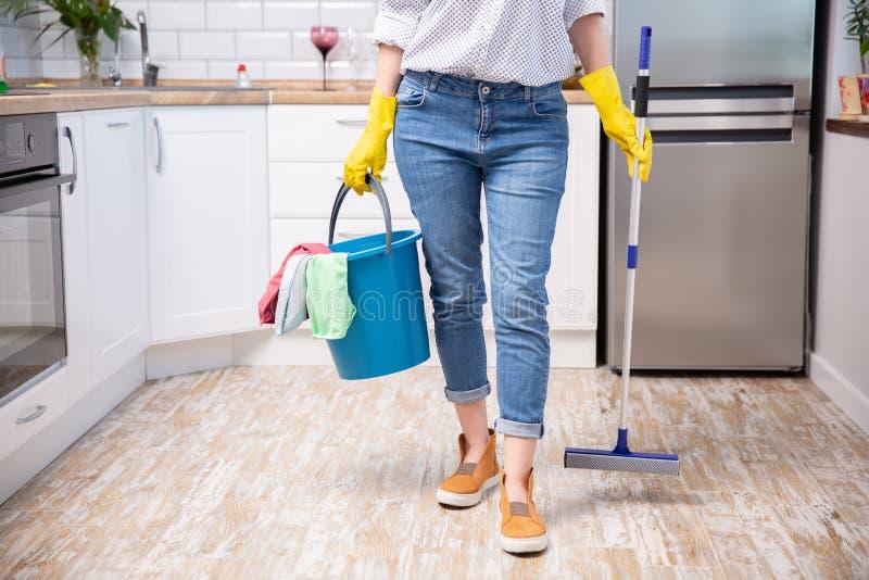 Jovem mulher com espanador e detergentes na cozinha, close up servi?o da limpeza fotos de stock royalty free