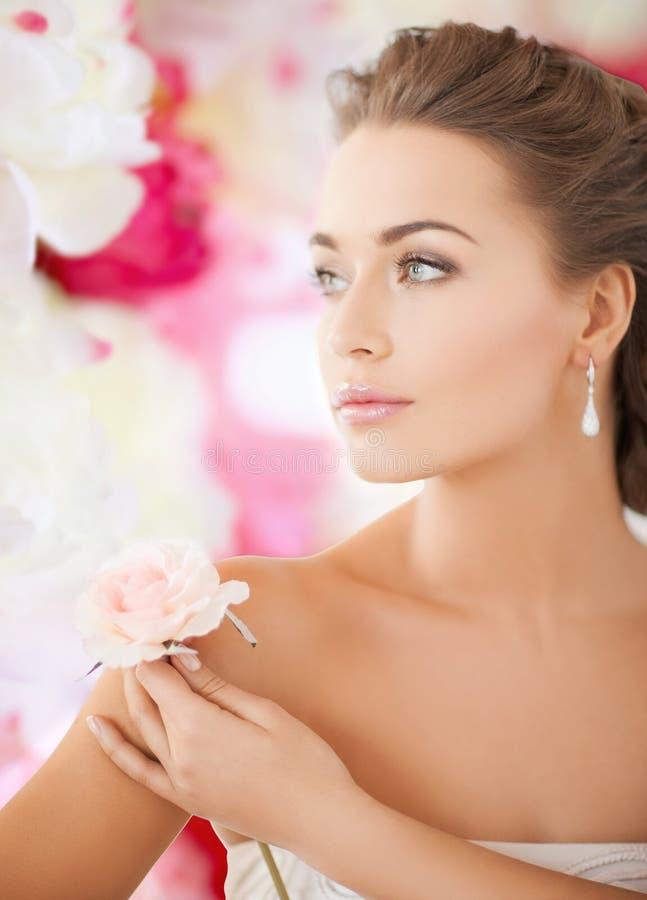 Jovem mulher com flor cor-de-rosa fotografia de stock