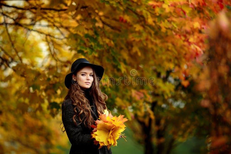 Jovem mulher com folhas de outono à disposição e fundo amarelo do jardim do bordo da queda imagem de stock royalty free