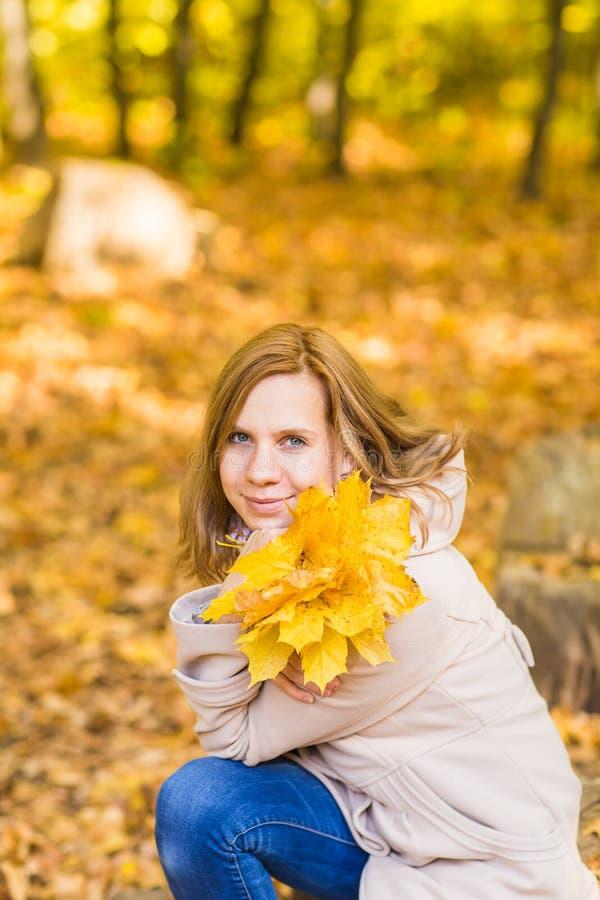 Jovem mulher com folhas de outono à disposição e fundo amarelo do jardim do bordo da queda foto de stock royalty free
