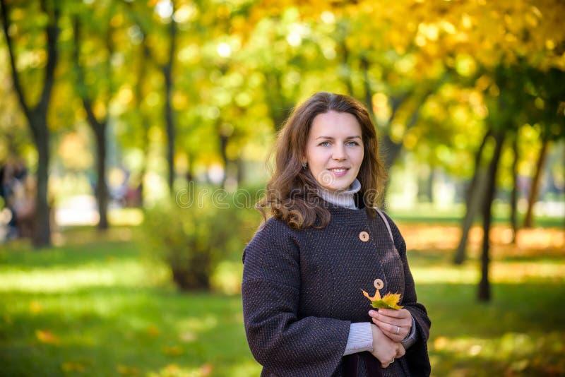Jovem mulher com folhas de outono ? disposi??o e fundo amarelo do jardim do bordo da queda foto de stock royalty free