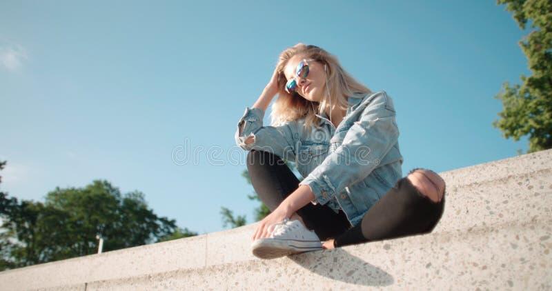Jovem mulher com fones de ouvido que aprecia o tempo em uma cidade fotografia de stock