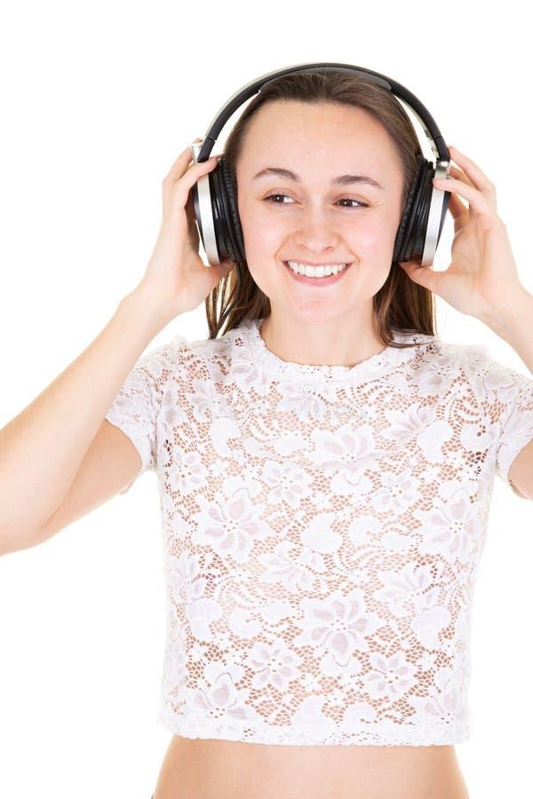 Jovem mulher com fones de ouvido que canta o adolescente bonito feliz da beleza foto de stock