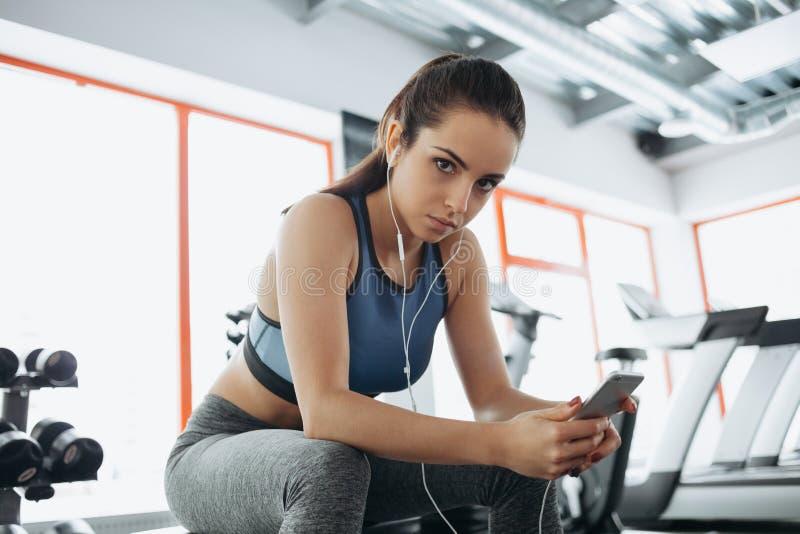 Jovem mulher com fones de ouvido que escuta a música após o exercício duro no gym fotografia de stock