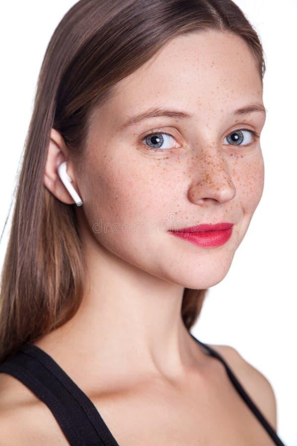 Jovem mulher com fones de ouvido sem fio imagem de stock