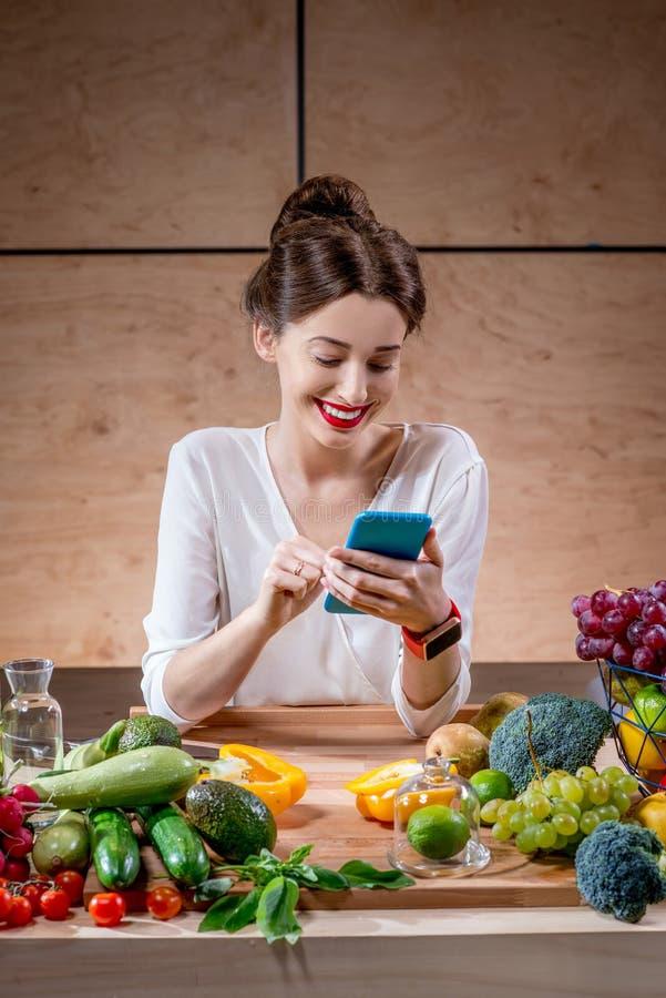 Jovem mulher com frutas e legumes na cozinha foto de stock
