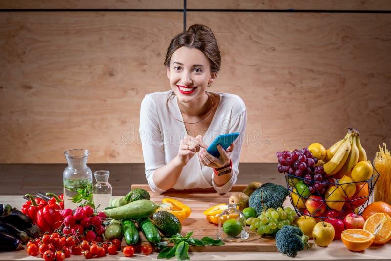 Jovem mulher com frutas e legumes na cozinha imagens de stock royalty free