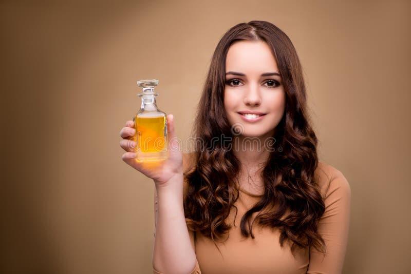 A jovem mulher com a garrafa do perfume fotografia de stock royalty free