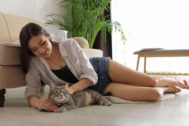 Jovem mulher com gato bonito em casa foto de stock royalty free