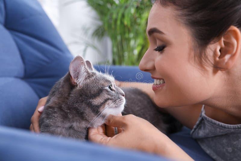 Jovem mulher com gato bonito em casa imagem de stock