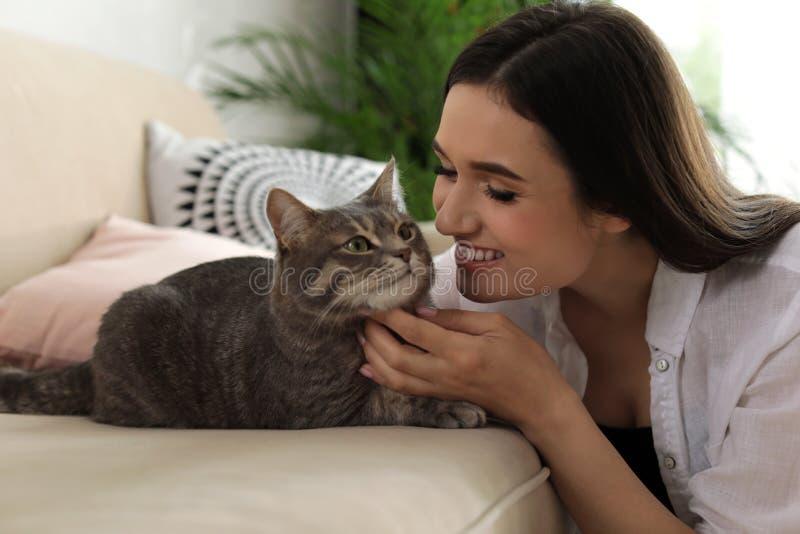 Jovem mulher com gato bonito em casa fotos de stock royalty free