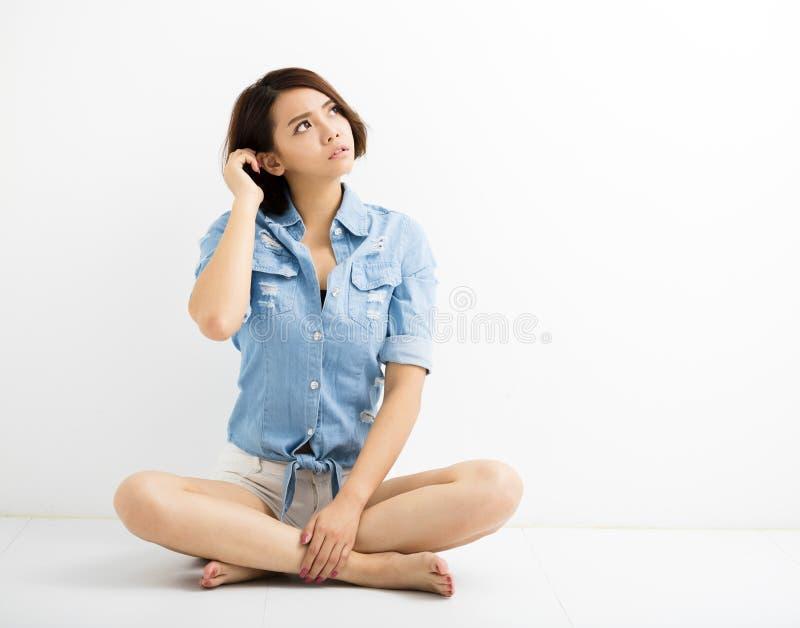 Jovem mulher com gesto confuso e assento no assoalho foto de stock