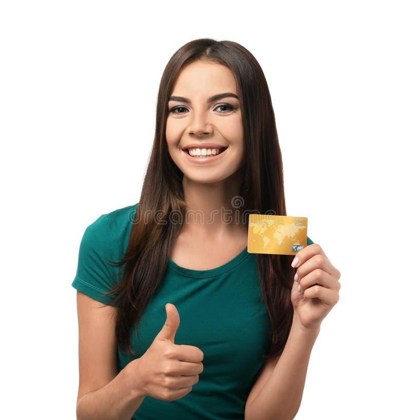 Jovem mulher com gesto do polegar-acima da exibição do cartão de crédito no fundo branco Compra em linha foto de stock royalty free
