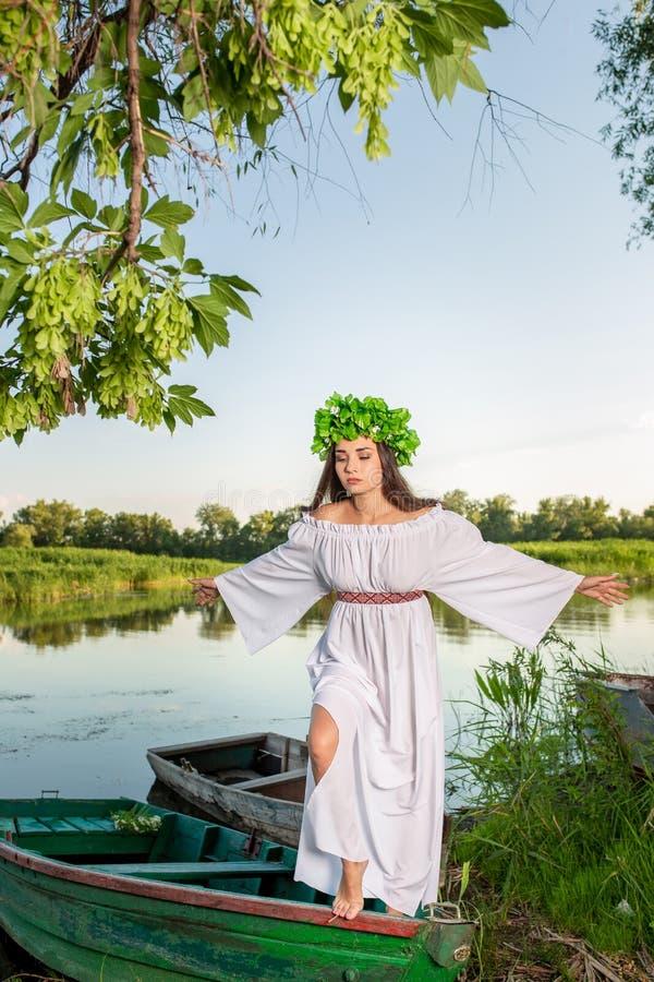 Jovem mulher com a grinalda da flor em sua cabeça, relaxando no barco no rio no por do sol Conceito da beleza fêmea, resto no fotografia de stock