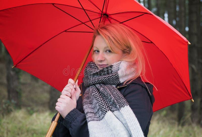 Jovem mulher com guarda-chuva vermelho em um dia de invernos chuvosos em uma floresta imagem de stock royalty free