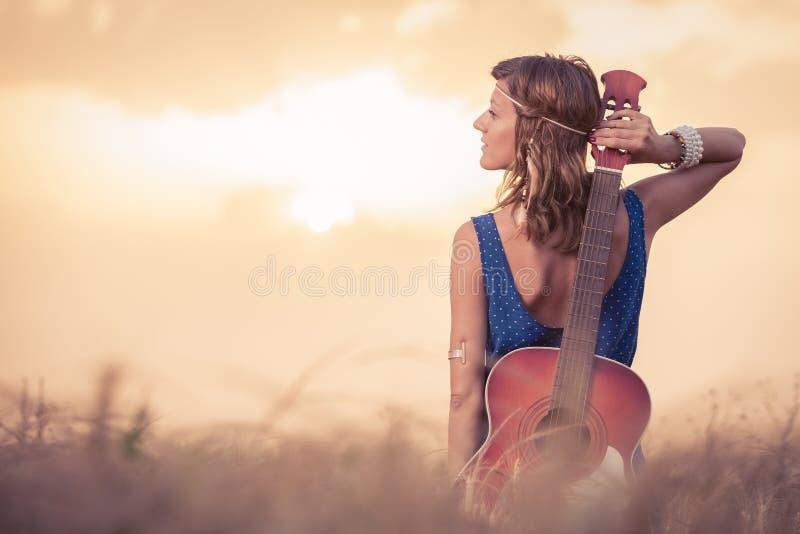 Jovem mulher com a guitarra acústica atrás dela que aprecia para trás a SU foto de stock royalty free