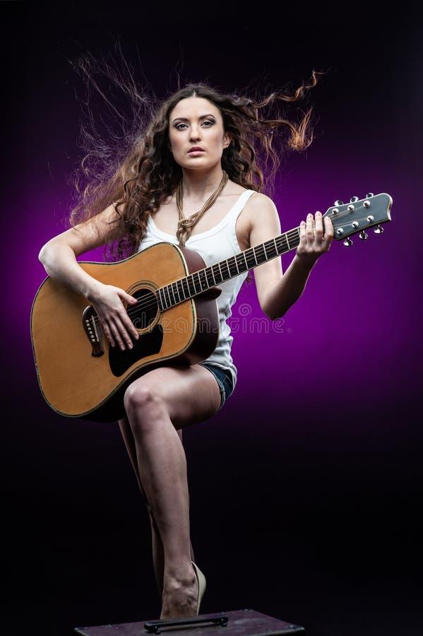 Jovem mulher com a guitarra, isolada no fundo preto e violeta fotos de stock