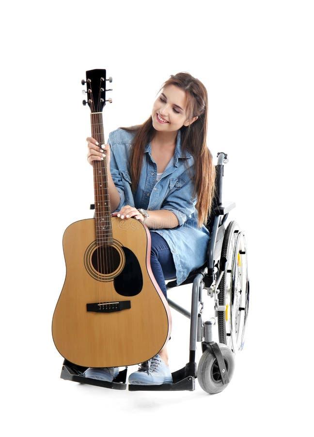 Jovem mulher com a guitarra que senta-se na cadeira de rodas no fundo branco fotografia de stock royalty free