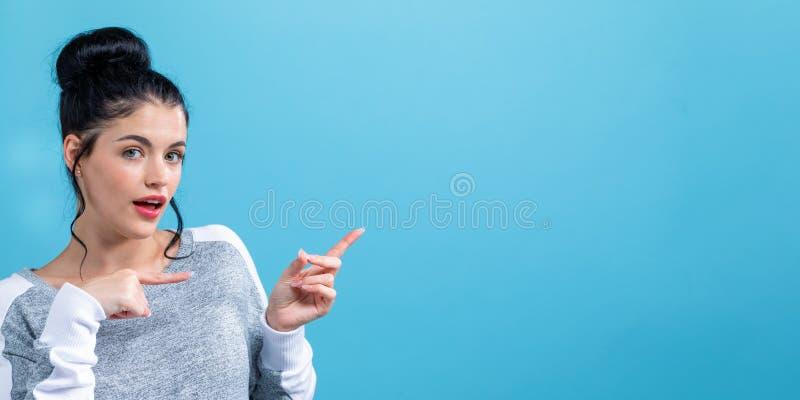 Jovem mulher com indicação do gesto de mão fotos de stock royalty free