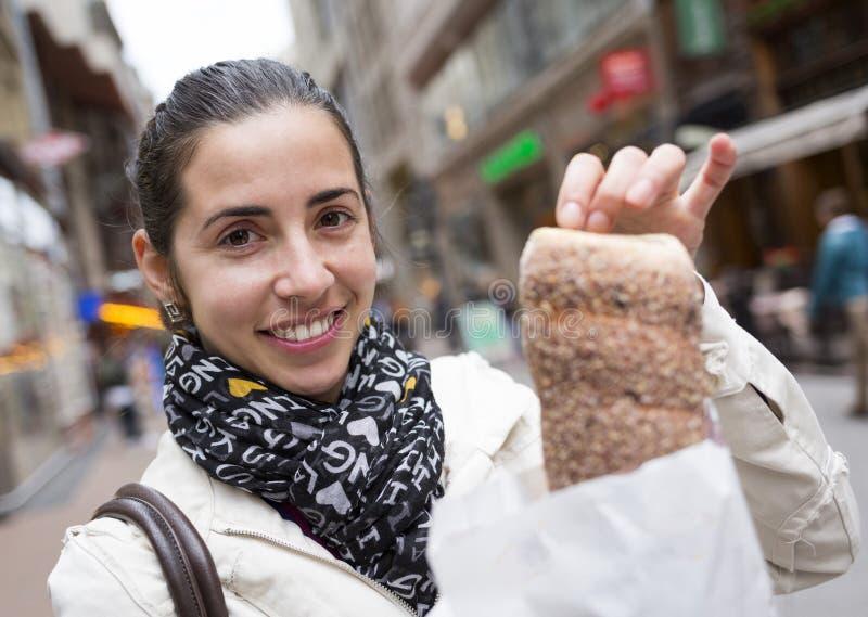 Jovem mulher com Kurtos Kalacs em Hungria imagem de stock