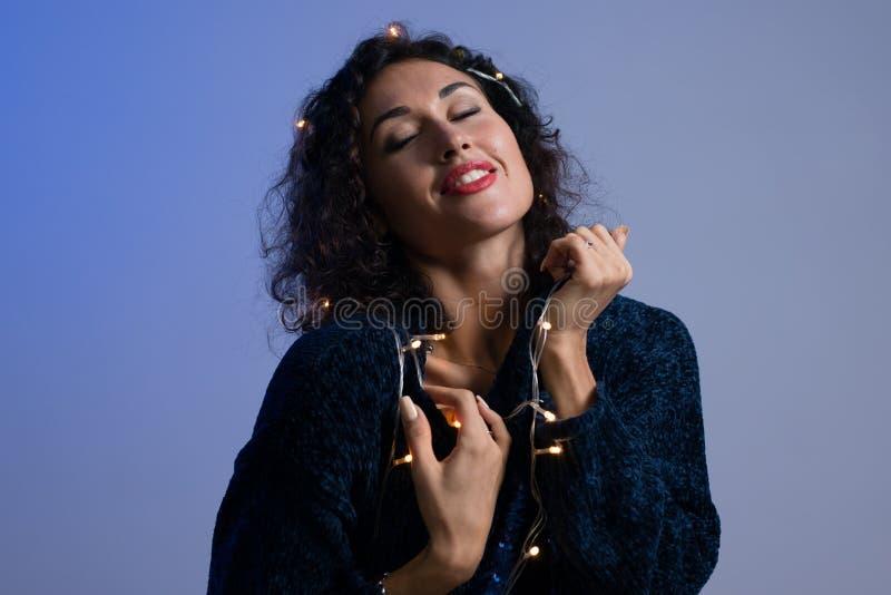 Jovem mulher com luzes de incandescência celebração do xmas, Natal, ano novo, aniversário imagem de stock royalty free
