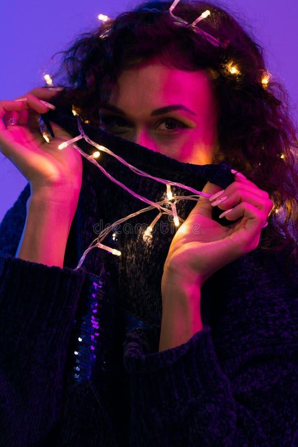 Jovem mulher com luzes de incandescência celebração do xmas, Natal, ano novo, aniversário fotografia de stock