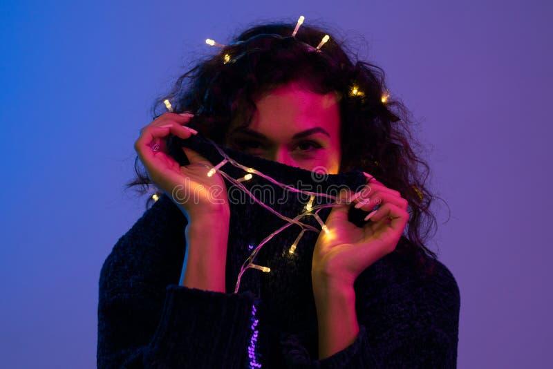 Jovem mulher com luzes de incandescência celebração do xmas, Natal, ano novo, aniversário imagem de stock