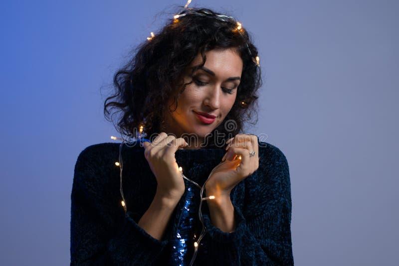 Jovem mulher com luzes de incandescência celebração do xmas, Natal, ano novo, aniversário foto de stock
