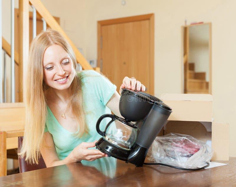 Jovem mulher com a máquina nova do café no interior home fotos de stock