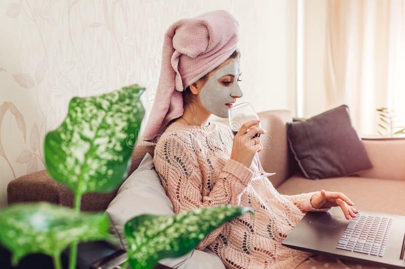 A jovem mulher com máscara facial aplicou o vinho bebendo ao usar o portátil no sofá Relaxamento em casa foto de stock