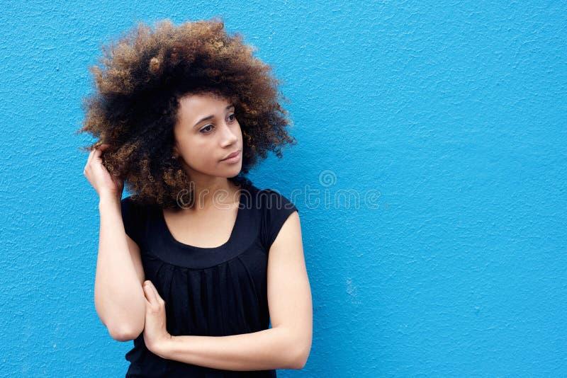 Jovem mulher com mão no cabelo afro imagem de stock