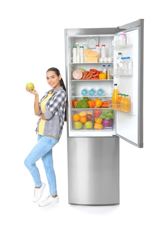 Jovem mulher com a maçã perto do refrigerador aberto foto de stock