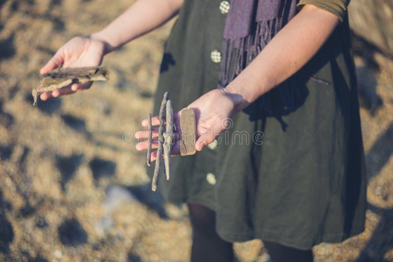 Jovem mulher com a madeira da tração encontrada na praia foto de stock