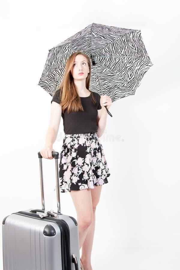 Jovem mulher com mala de viagem e guarda-chuva no fundo branco fotos de stock royalty free