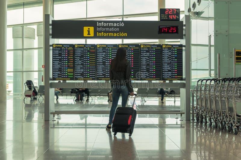 Jovem mulher com a mala de viagem no sal?o da partida no aeroporto conceito do curso fotografia de stock