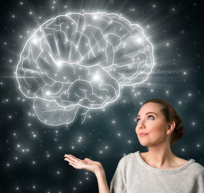 Jovem mulher com o cérebro de incandescência grande foto de stock