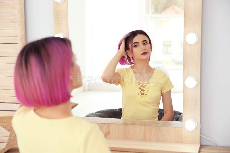 Jovem mulher com o cabelo da cor que olha no espelho fotografia de stock