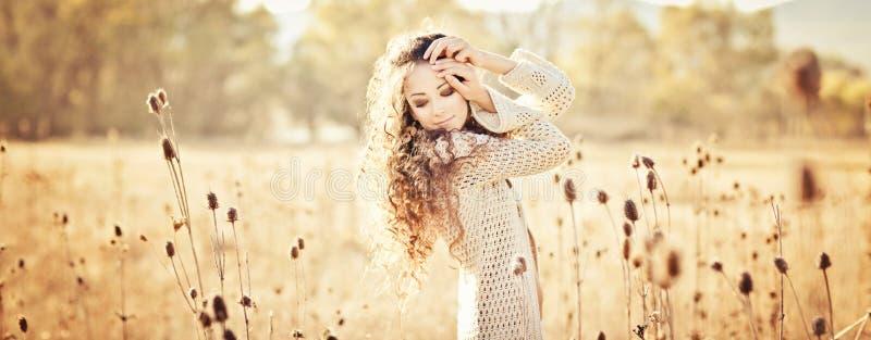 Jovem mulher com o cabelo encaracolado bonito que levanta no campo no por do sol fotografia de stock royalty free
