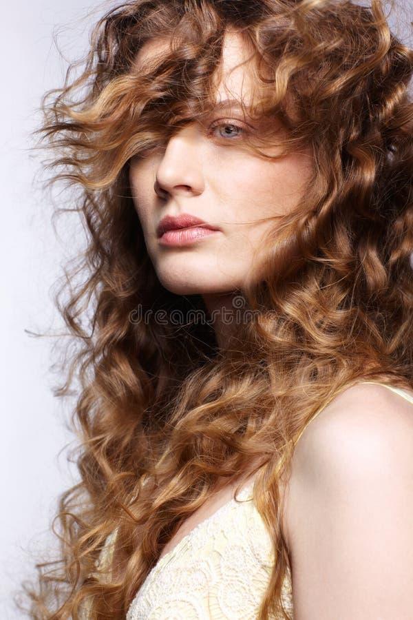 Jovem mulher com o cabelo encaracolado dourado longo que vibra no vento fotos de stock royalty free