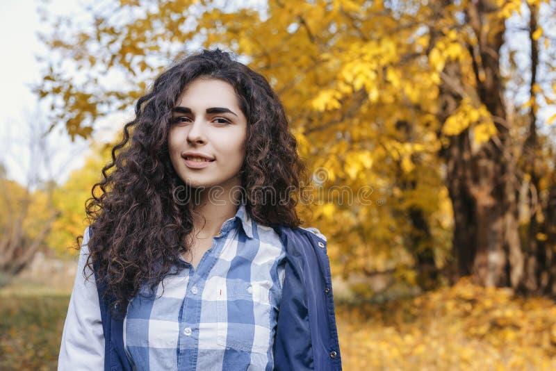 Jovem mulher com o cabelo encaracolado longo que está no parque do outono fotos de stock royalty free
