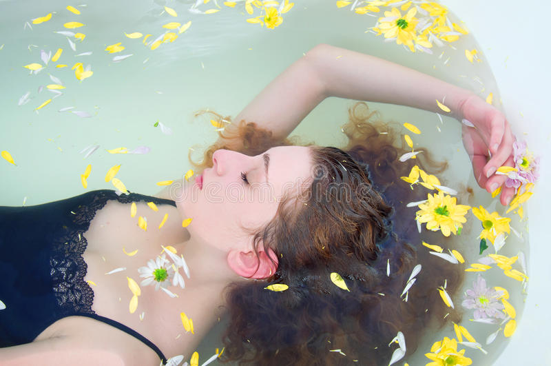 Jovem mulher com o cabelo encaracolado que toma um banho com ervas fotografia de stock royalty free