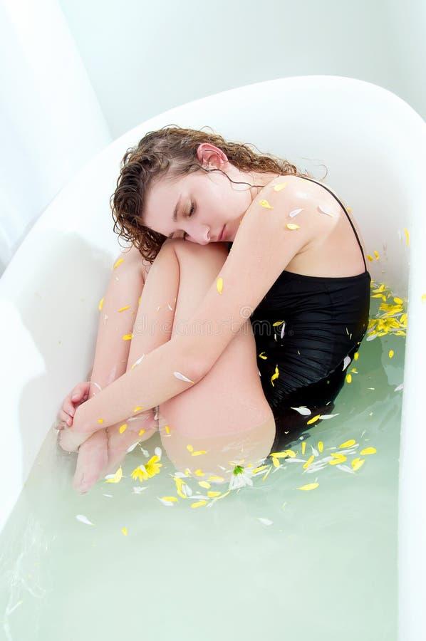 Jovem mulher com o cabelo encaracolado que toma um banho com ervas imagens de stock royalty free