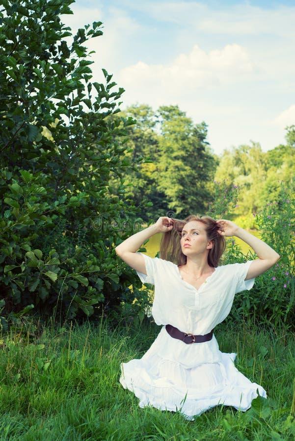 Jovem mulher com o cabelo longo que senta-se na grama foto de stock