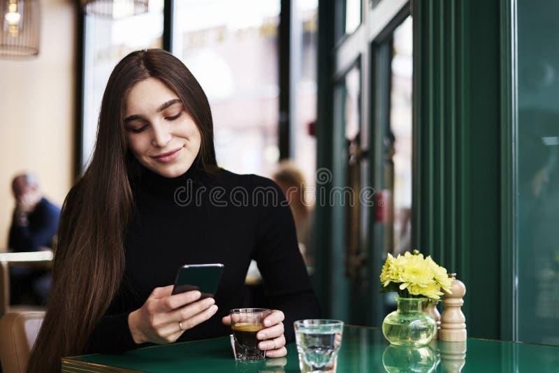 Jovem mulher com o cabelo longo que texting pelo telefone celular, sorrindo, café bebendo que tem o resto no café perto da janela fotos de stock