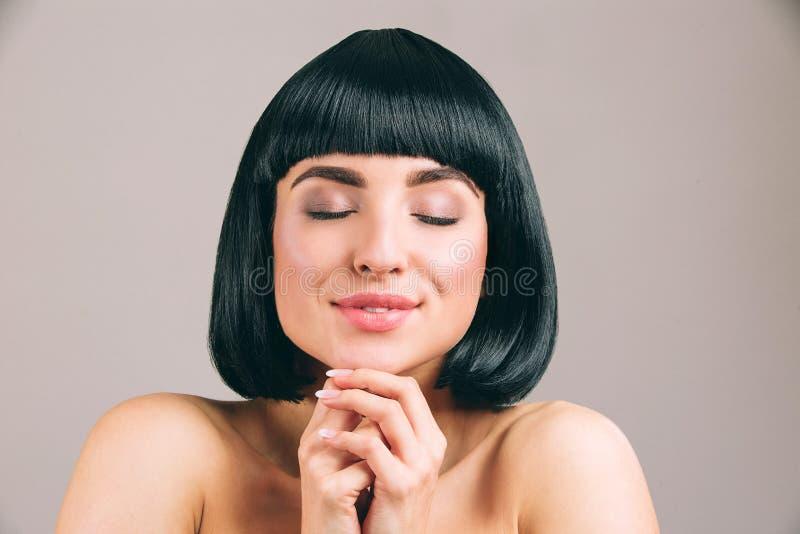 Jovem mulher com o cabelo preto que levanta na c?mera O modelo agradável sonhador mantém os olhos fechados e as mãos junto Sorris foto de stock royalty free
