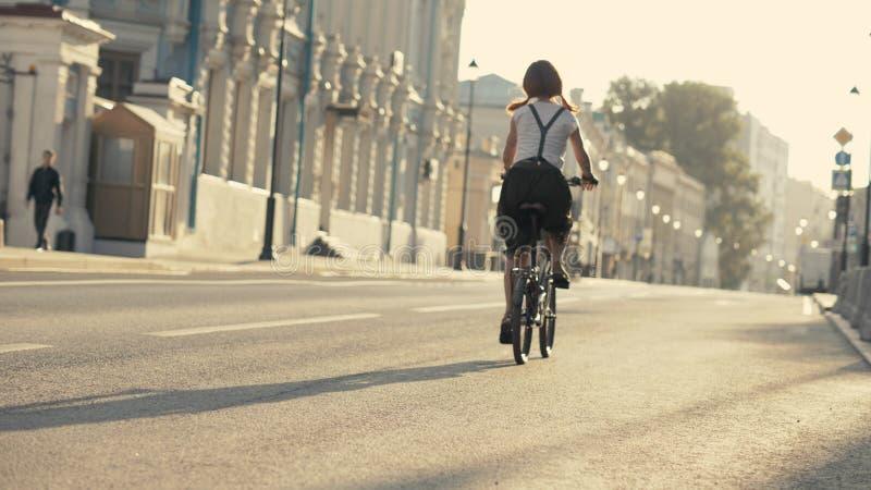 Jovem mulher com o cabelo vermelho que monta uma bicicleta na opinião inferior do parque Parque da bicicleta da mulher foto de stock royalty free