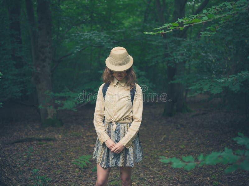 Jovem mulher com o chapéu do safari na floresta fotografia de stock royalty free