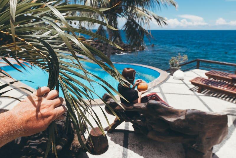 Jovem mulher com o coco que relaxa na piscina nas horas de verão Férias na ilha de Bali, Indonésia fotografia de stock royalty free