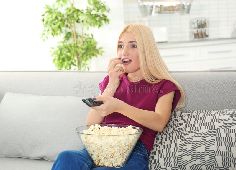 Jovem mulher com o controlo a distância e a bacia de pipoca que olham a tevê no sofá fotos de stock